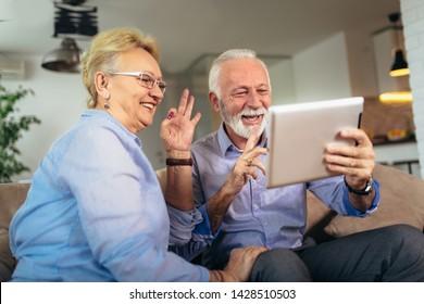Smiling deaf senior couple talking using sign language on the digital tablet's cam