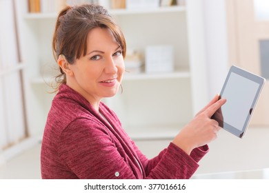 Smiling Deaf woman using tablet at home