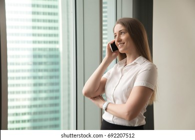 Smiling delighted businesswoman talking on cell while standing at office window, happy female manager making answering call in mobile roaming, lady having pleasant phone conversation with client