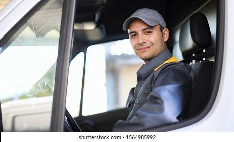 Smiling deliverer driving a van