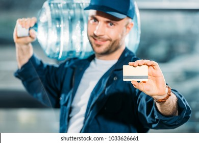 Smiling delivery man holding water bottle and showing credit card