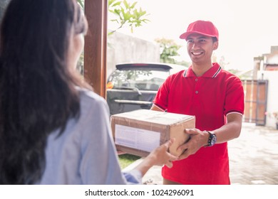 Smiling delivery man in red uniform delivering parcel box to recipient