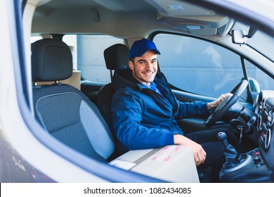 Smiling delivery man sitting in the car as a driver