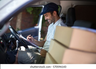 Smiling delivery man writing in clipboard while sitting in van