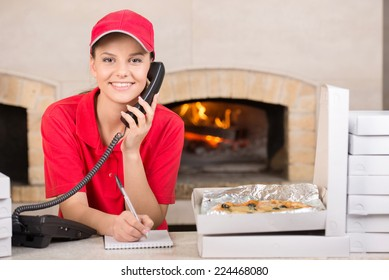 Smiling delivery young woman of pizza on the phone. The boxes of pizza on the table.