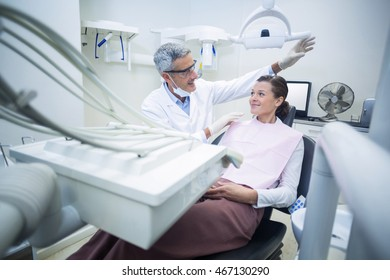 Smiling dentist talking to patient in dental clinic