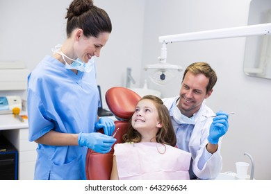 Smiling dentists interacting with young patient in dental clinic
