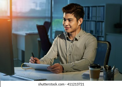Smiling designer  drawing on tablet and looking at computer screen