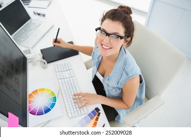 Smiling designer using computer and digitizer in the office