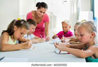 Smiling diligent kids learning to write on lesson in elementary school class