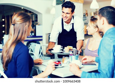 Smiling diligent waiter showing hospitality and serving visitors in cozy coffeehouse