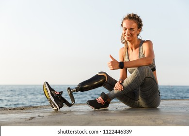 Smiling disabled athlete woman with prosthetic leg showing thumbs up while sitting at the beach