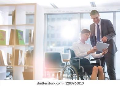 Femme d'affaires souriante et handicapée discutant sur une tablette numérique avec un homme d'affaires au bureau avec une lampe à incandescence en arrière-plan