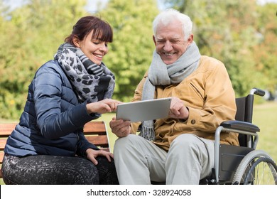 Smiling disabled man and caregiver with a tablet