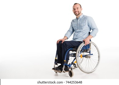 smiling disabled man in wheelchair looking at camera, isolated on white