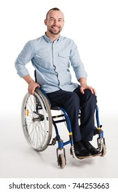 smiling disabled man in wheelchair looking at camera isolated on white