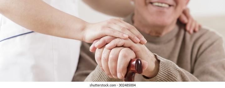 Smiling disabled senior man and caring nurse