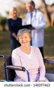 smiling disabled senior woman outdoors with her daughter and doctor on background