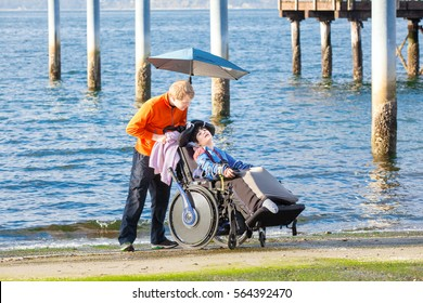 Smiling disabled ten year old  boy in wheelchair being cared for by  friend or  family outdoors near ocean,  water in background.