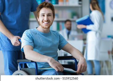 Smiling disabled young man on wheelchair at the hospital, a doctor is assisting him