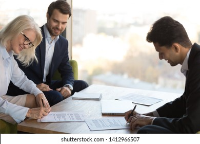 Smiling diverse business partners put signature on paper contract closing deal in office, finalize successful negotiation, happy businesspeople sign agreement, fill in document at briefing