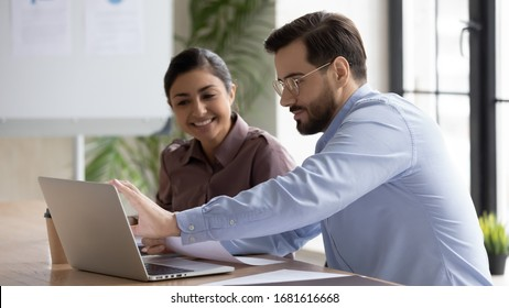 Smiling diverse businesspeople sit at desk work on laptop together discussing project or idea, happy multiracial colleagues cooperate using computer gadget, brainstorm at office meeting