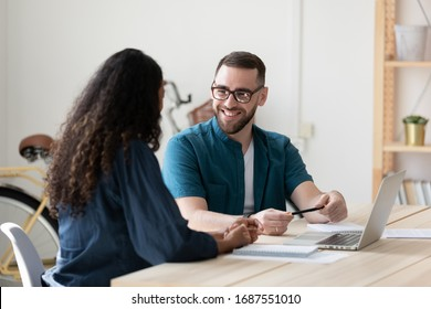 Smiling diverse businesspeople sit at desk laugh brainstorming working together on laptop at meeting, happy colleagues have fun discuss business ideas or project, cooperating on computer at briefing