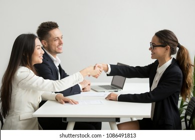 Smiling diverse businesswomen shake hands at group meeting, friendly asian hr handshaking congratulating hired applicant at job interview, satisfied millennial partners make contract deal concept