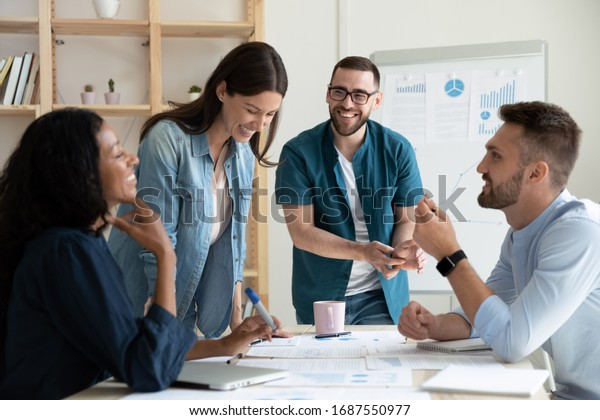 Smiling diverse colleagues gather in boardroom brainstorm discuss financial statistics together, happy multiracial coworkers have fun cooperating working together at office meeting, teamwork concept