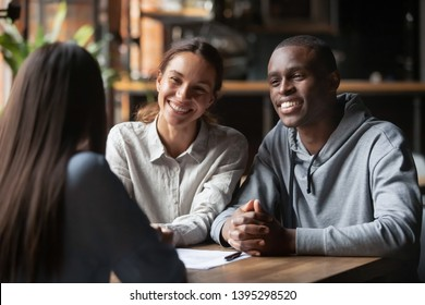 Smiling diverse couple listening to financial advisor or realtor at meeting in cafe, African American husband and wife taking loan or mortgage, successful negotiations with lawyer or insurance broker
