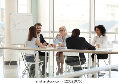 Smiling diverse employees group talking sit at meeting table in modern space conference room, happy african and caucasian team coworkers business people collaborating at office corporate briefing