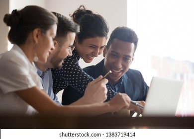 Smiling diverse employees have fun joking discussing ideas brainstorming on computer at meeting, happy multiethnic colleagues laugh watching funny video on laptop together during break in office