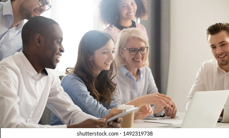 Smiling diverse employees listening to businesswoman coach at briefing, mentor explaining strategy, training staff, using laptop, helping with software, team building activity, horizontal photo