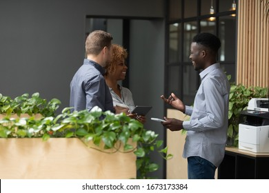 Smiling diverse employees talking, chatting in modern office during break, happy African American businessman sharing good news, discussing project with colleagues, having pleasant conversation
