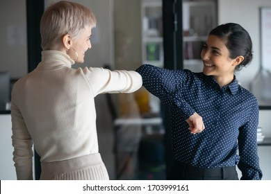 Smiling diverse female employees greeting bumping elbows at workplace, happy woman colleagues say hello in office, protect from coronavirus COVID-19 pandemic, corona, healthcare concept