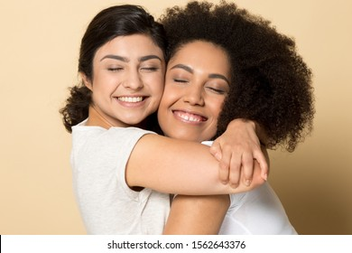 Smiling diverse girls with closed eyes, best friends hugging close up, standing isolated on brown studio background, two young female expressing love and support, true friendship, good relations