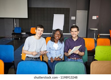 Smiling diverse men and woman on colorful seats in modern conference hall smiling at†camera