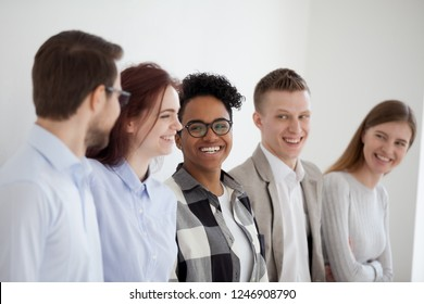 Smiling diverse millennial people standing in row near wall talking or joking, excited multiracial young employees have fun laughing, happy workers team or group chat looking at each other in office