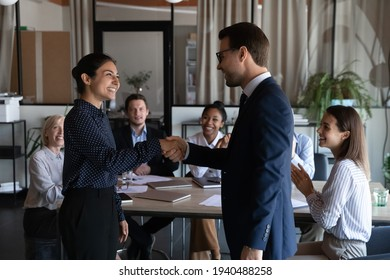 Smiling diverse multiracial employees handshake close deal agreement at meeting. Happy multiethnic businesspeople shake hand get acquainted greet at briefing, congratulate colleague with promotion.