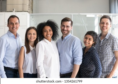 Smiling diverse office workers group, multiracial team of employees looking at camera, motivated successful business people, staff posing together in modern office, multi-ethnic colleagues portrait