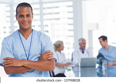 Smiling doctor with arms crossed standing in front of his team