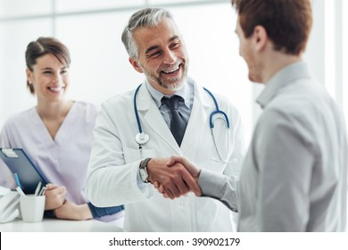 Hymyilevä lääkäri klinikalla antaa kädenpuristus hänen potilaan, terveydenhuollon ja ammattitaidon käsite