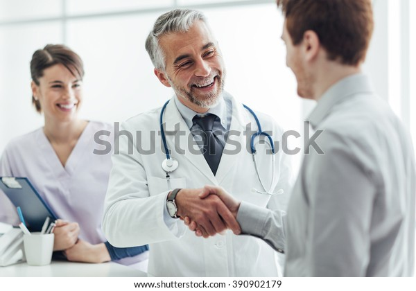 Smiling doctor at the clinic giving an handshake to his patient, healthcare and professionalism concept