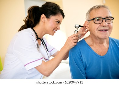 Smiling doctor exam ear with otoscope at clinic of nursing home