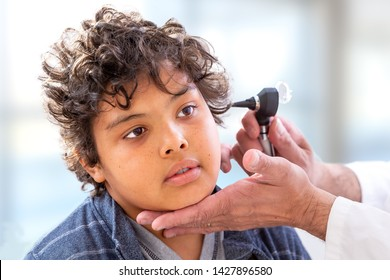 Smiling doctor examining little boy's ears at the practice