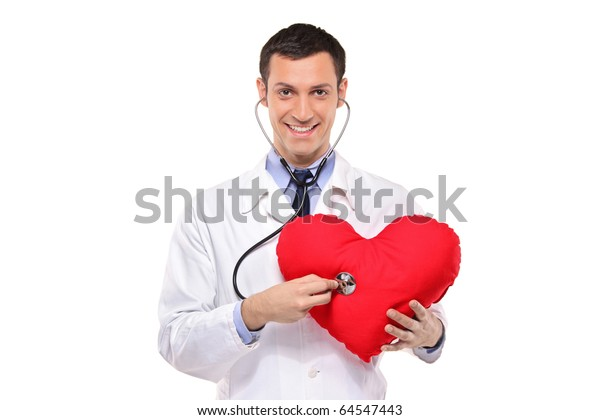 A smiling doctor examining a red heart shaped pillow with a stethoscope against white background