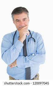 Smiling doctor with hand on chin is thinking