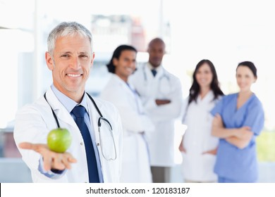Smiling doctor holding an apple while his team is looking at him