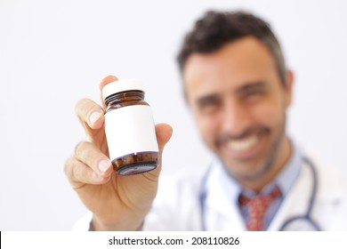 Smiling doctor holding up a bottle of tablets or pills with a blank white label for treatment of an illness or injury with focus to the bottle