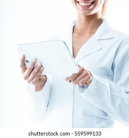 smiling doctor holding a digital tablet and tapping with her index finger